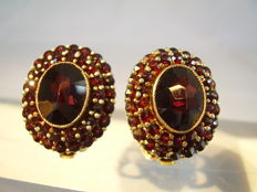 Antique big ear clips with round and oval faceted garnets in the antique rose cut of 12 ct in total.
