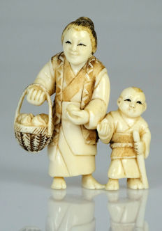 Ivory netsuke - Lady with basket of fruits and child with sword - signed - Japan - ca. 1920