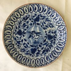 Delftware plate with central a putto, the Netherlands, second half of 18th century.