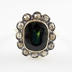 18 kt gold entourage ring with large, dark blue-green sapphire of 2.5 ct and 0.60 ct old European cut diamonds set in platinum