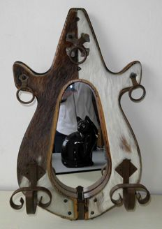 Wooden and wrought iron mirror covered with cowhide. In the shape of a horse barrier in teardrop shape