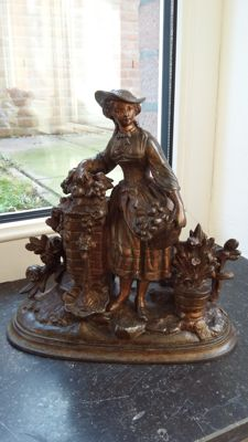 Beautiful zamak sculpture of an elegant young lady resting at a fountain