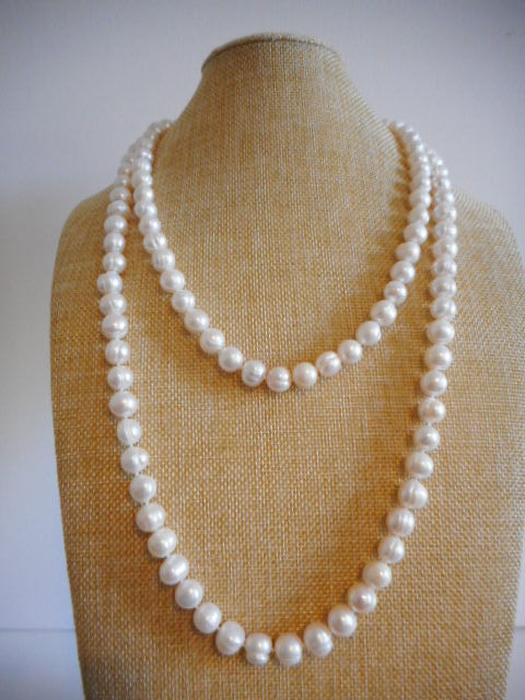 Pearl necklace of white baroque cultured fresh water pearls with a 14k gold clasp, 123 cm in length.