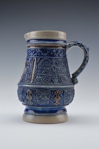 Westerwald gres porcelain jug with one handle - body decorated with a proverb and leaf - and with floral motifs in blue and brown enamel