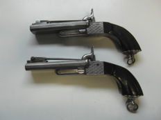 Two double-barrelled percussion pistols with folding daggers in the original excellent condition