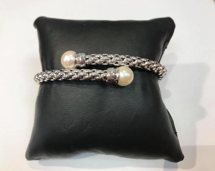 A white gold bracelet with rigid links and salt water pearls on the ends, approx. 0.75 in diameter.