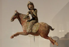 Painted Red Pottery Female Polo Player Astride a Galloping Horse - Length 30 cm.