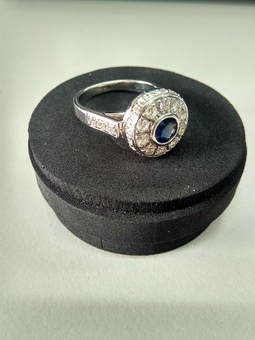 Exclusive Pumori ring made of 18 kt white gold. (750/1000). Central blue round sapphire measuring 5.60 mm and 0.75 ct. 27 diamonds measuring 1.50 mm and 0.01 ct.  6 diamonds measuring 2.0 mm and 0.03 ct 10 diamonds measuring 2.50 mm and 0.06 ct, with a diameter of 13.80 mm Weight 8.36 g Available for resizing.