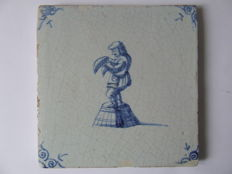 Antique tile with a depiction of a town crier on a basket