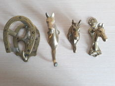 Set of four pieces including a door knocker and three brass bridle hooks with a horse head shape