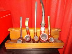 A collection of 5 pipes with stand