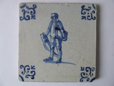 Antique tile with a fisherman and his fillet board