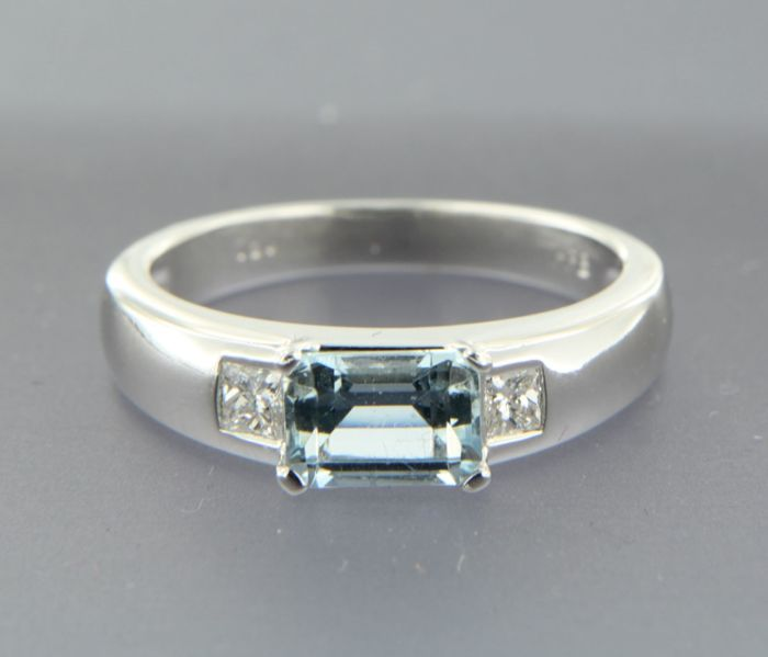 18 kt white gold ring, set with blue topaz and two princess-cut diamonds of approx. 0.20 ct in total, ring size: 16.5 (52)