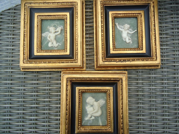 three alabaster putti paintings of angels in gold coloured baroque