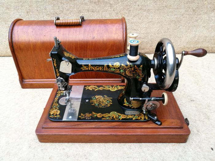 Singer sewing machine with a wooden dust cover, 1891