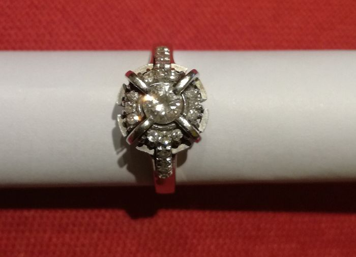 18 kt white gold ring with brilliant cut diamonds. The central diamond is 0.20 ct, colour D. With 21 diamonds, 0.01 ct, colour D.