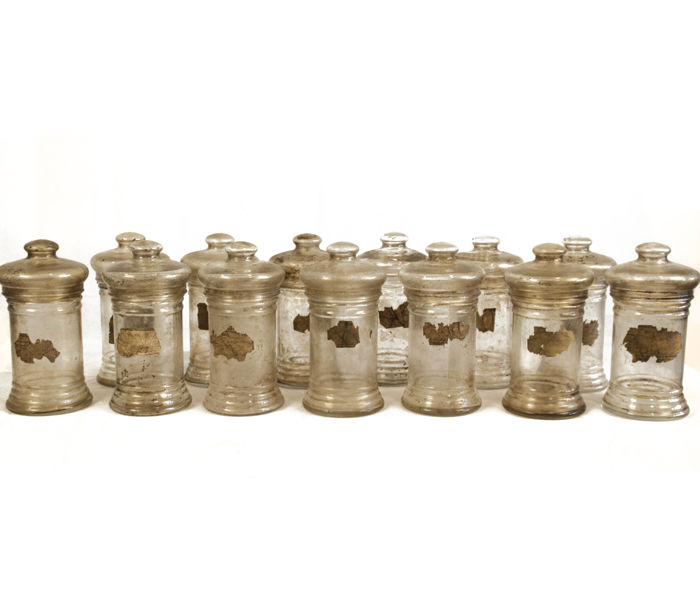 Collection of 13 old pharmacy glass jars.