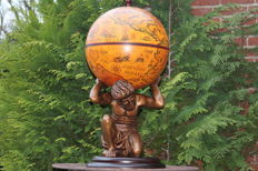 Large decorative bar globe carried by atlas with images of a map from circa 1600, very detailed