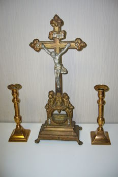 Large metal cross and two copper candlesticks.