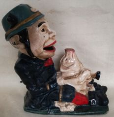 Cast iron piggy bank - man with a pig, the pig shoots the coin in the mouth of the man with his foot