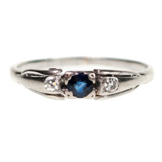 This beautiful ring features 0,07ct Sapphire decorated with two 0,04ct Single Cut Diamonds in 14k white Gold.