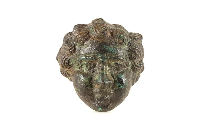 Roman bronze applique in the shape of the face of eros 51 mm
