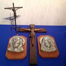 Two religious plaques of polished aluminium on wood, a large copper crucifix and wood, and a standing crucifix.