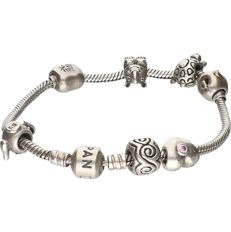 925/1000 Silver Pandora bracelet with various charms of which 2 have gold details. - length x width: 19 x 0.3 cm