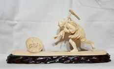 Large ivory Okimono of villager chasing a hat - Japan - Late 19th/early 20th century (Meiji Period)