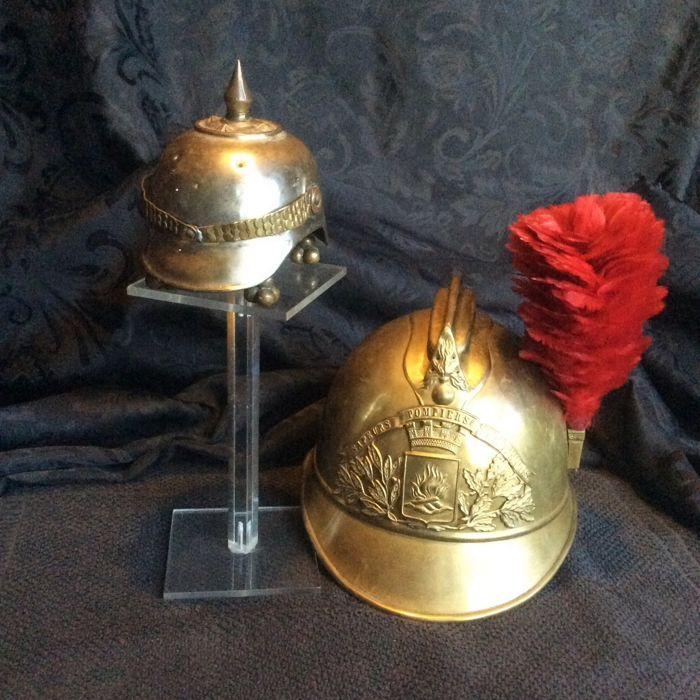 1 small spiked helmet, German date on the visor 16/9 1889 and 1 officer firefighter helmet 1895 and its plume