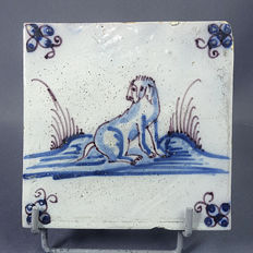 Tile with decoration of a dog in blue.