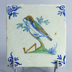 Tile with polychrome decoration of a bird on a branch.