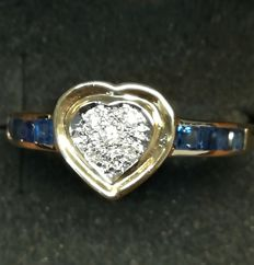 18 kt gold cocktail ring - Total weight: 2.1 g - Ring size: 14 - Total number of stones: 13 - Five diamonds in brilliant cut and eight sapphires in carré cut - Heart-shaped border