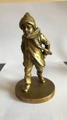 A bronze sculpture of boy, in winter clothing - circa 1920