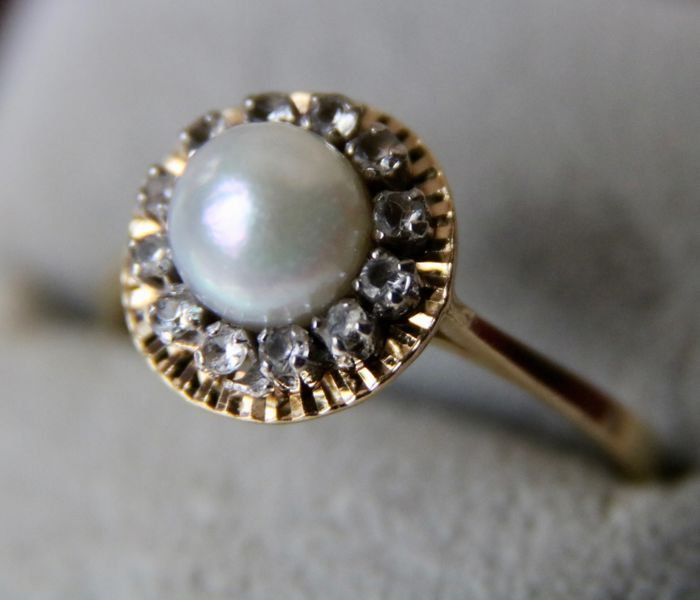 Antique 14Kt. gold ring set with an Akoya sea pearl and surrounded by 12 Sapphires.