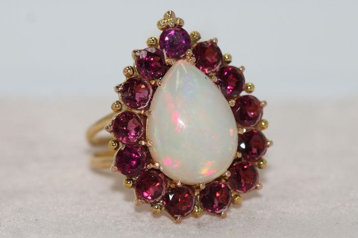 18 kt gold entourage ring set with garnets and an opal of 6 ct - ring size: 60
