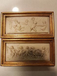 Two resin relief pictures depicting putti playing