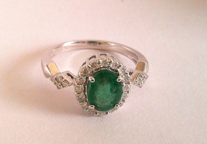 14kt white gold ring set with an Emerald and 24 brilliant cut diamonds. Ring size is 17mm.