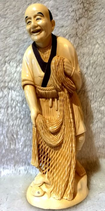 Large polychrome, ivory okimono depicting a fisherman with net and fish - Japan - circa 1920-1930