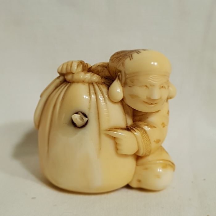 Marine ivory netsuke - Daikoku with a sack from which a mouse is sticking out - Japan - late 19th century (Meiji Period)