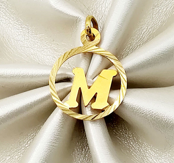 "18 kt yellow gold pendant, circular shape with letter ""M"". Diameter 1.70 cm. Total weight 1.77 g"