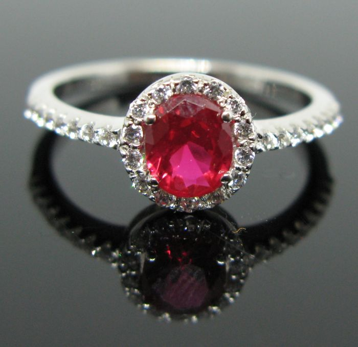 18 KT white solid gold ring set with 1 ruby round faceted-cut 0,80 ct and 30 white sapphires round-brillant cut tot 0,30 ct. Size: 14 (54)