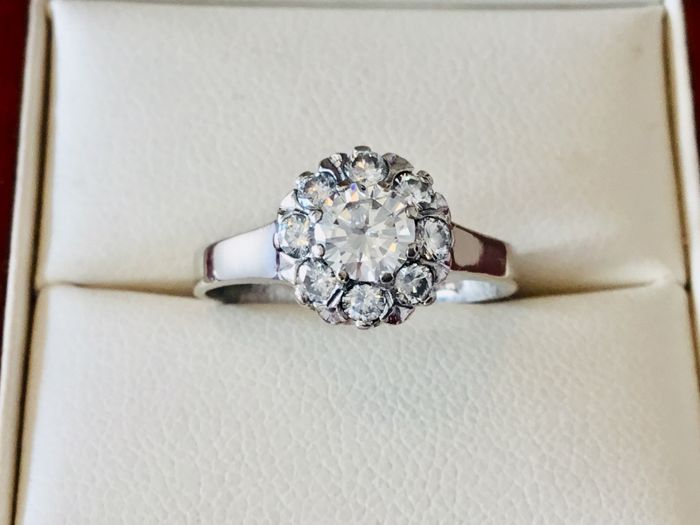 18 kt white gold entourage ring with brilliant cut centre stone of 0.47 ct and 8 of 0.035 ct, in total 0.75 ct, E-F/VVS very lively diamonds. Ring size: 17.50 mm
