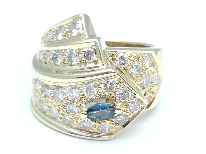 18 kt wide cocktail ring with 32 brilliant cut diamonds totalling 0.74 ct. and 1 marquise cut blue sapphire.