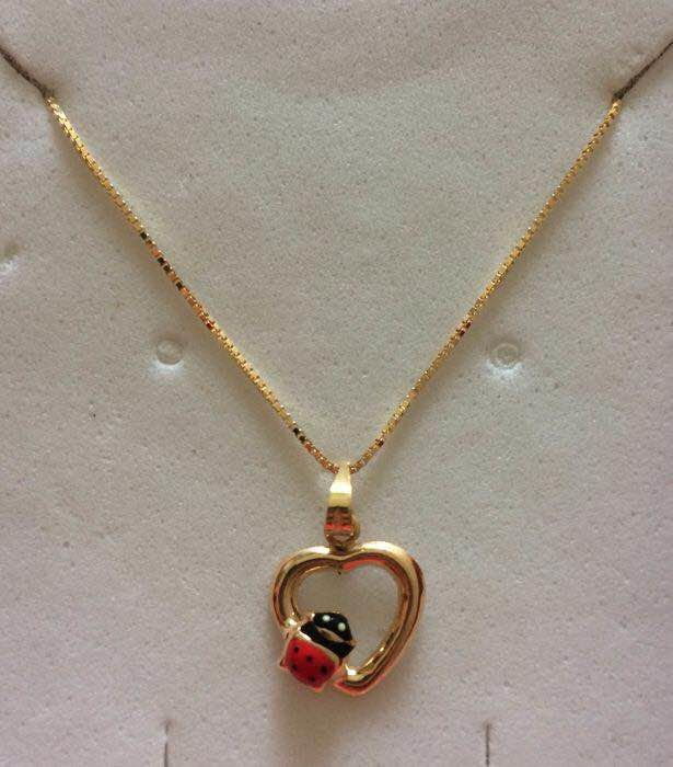 Yellow gold necklace (18 kt) with heart shaped pendant featuring a ladybird