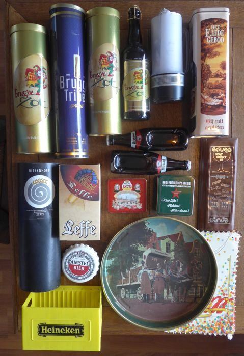 Collection of beer advertising items, beer glasses and cans, coasters