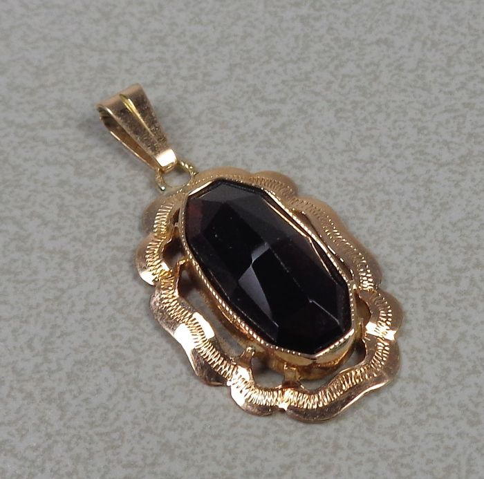 14 kt gold pendant with garnet.