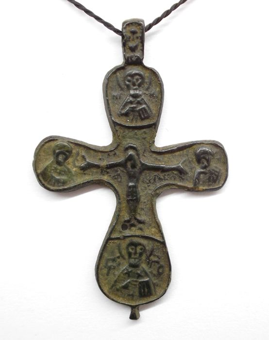 medieval bronze cross with crucified jesus and the faces of the