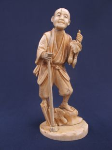 Signed ivory okimono, man with harvest and stick in his hand Japan - late 19th century (Meiji period)