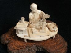 A higly detailed small ivory okimono of a dollmaker, signed - Japan  - ca. 1900 (Meji period)